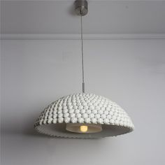 Hanging lamp made with land snails by Respiga ecodesign.