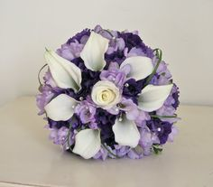 wedding bouquet of ivory calla lilies with lilac freesia, purple lisianthus, loops of grass and a touch of sparkle