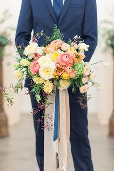 Groom in a Navy Blue Suit with a Colorful Citrus Bouquet