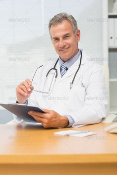 Buy Concentrating mature doctor sitting at his desk with clipboard in his office at the hospital by Wavebreakmedia on PhotoDune. Concentrating mature doctor sitting at his desk with clipboard in his office at the hospital Medical Photography, Product Photography, Doctor Images, Headshot Poses, Health Icon, Male Doctor, Pediatric Dentist, Corporate Headshots, Business Portrait