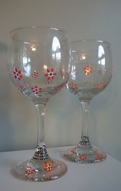 Orange & red floral design hand painted on these wine glasses. Notice the bottoms are the same, the tops are different colors so you can remember which glass is yours.