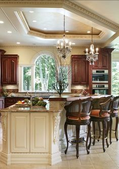 Beautiful kitchen. Love the mini chandeliers and warm tones.