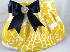 * Pleats give this clutch a gorgeous shape.   * Made from drapery weight (canvas weight) cotton and has an Amsterdam Damask print in the colors of corn yellow and white.   * The lining is made from a white cotton weight solid fabric.   * Accented with a gorgeous navy satin bow and clear crystal.
