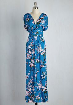 Glide through your day feeling dreamy as can be in this printed maxi dress! An ethereal print of soft pink cherry blossoms and black branches adorns the rich cerulean silhouette of this V-necked, short-sleeved frock, creating a look that is both vibrant and poised.