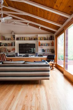 stripe sofa in a living room with vaulted ceiling