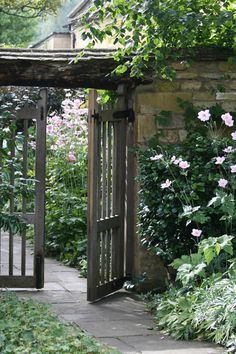 Timber garden gate between the wisteria and the garage at the path leading to the back garden