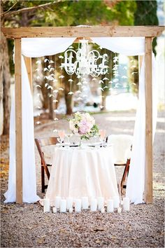 Rustic Sweetheart Table. Everything about this is gorgeous! Love the romantic white draping, the chandelier, and the candles in front of the table.