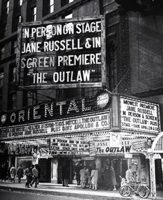 """A theater marquee advertising the movie """"The Outlaw."""" Photograph by Wallace Kirkland. New York City, 1946."""