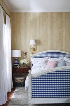 The bedroom in this 105-year-old Victorian farmhouse has a white-painted bed covered in a graphic blue-and-white-check fabric and wood grain wallpaper to create a warm backdrop.