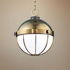 The Sumner industrial pendant light in aged brass finish is a globular hanging lighting structure by Hudson Valley Lighting.