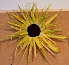 lightly enchanted: sunflower made from corn husks painted yellow and hot glued around a metal ring.