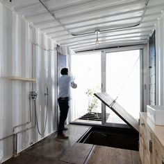 with a tight budget, recycled materials and reclaimed metal shipping containers were used to construct a house whose connections and construction remain exposed.