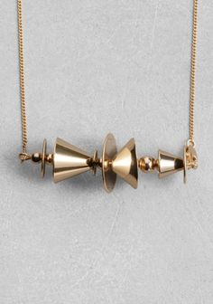 A luxe necklace made from shiny brass featuring a clash of conic shapes.