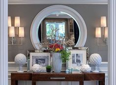 round mirror. wall covering. wainscoting. neutrals. sconces. by ruby
