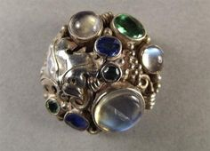 Dorrie Nossiter (attrib.). A silver brooch set with moonstones and semi-precious stones. The vendor states 'This may have been a hat pin but now bears a brooch pin.' Diameter 1 in. Sold by Barbara Kirk Auctions. This is similar to the panel that was converted into a ring (see adjoining pin to this one).