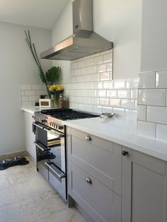 Grey burford kitchen with White corian worktops and subway tiles