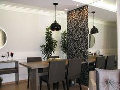 Espelhos e mesa encostada na parede: combinação perfeita para ampliar o cômodo e aproveitar bem os espaços.