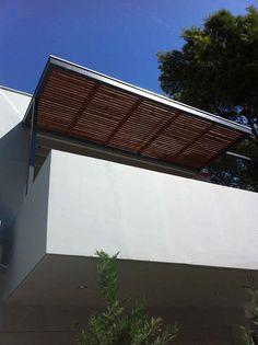 Μεταλλικό στέγαστρο σε μπαλκόνι με οριζόντιες ξύλινες σανίδες ως σκίαση και κάλυψη με πολυκαρβονικό.