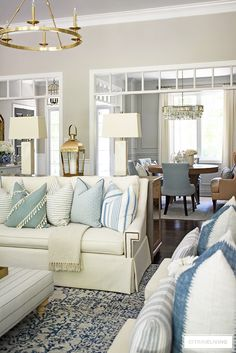 Open concept living room decorated fir summer with light blue, white, creams, ivories featuring pillows with stripes and mixed patterns. Blue And Cream Living Room, Ivory Living Room, Table Decor Living Room, Coastal Living Rooms, Home Living Room, Living Room Designs, Blue And White Pillows, Room Tour, Decoration