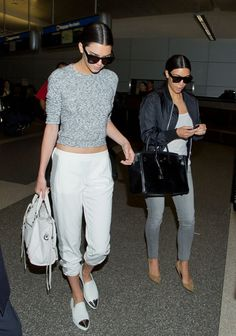 Out with her sister, Kendall Jenner keeps it cute with a crop sweater, track pants, and pointy-toe metallic slip-ons