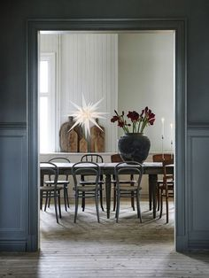 Artilleriet is just the dream | Rustic yet minimal scandinavian dining room | mismatched bentwood chairs | paper star and seasonal flowers add a festive touch
