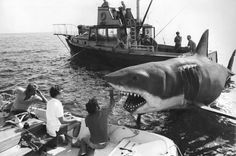 """"""" JAWS """" 1975 ~ The Shark AKA """" BRUCE """" being checked over for malfunctions due to all the salt water as the cast patiently wait on the Orca and nervous Spielberg ( in white ) waiting to get up and running again."""