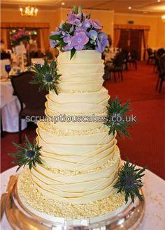 www.scrumptiouscakes.co.uk (973) - 4 tier white chocolate wrap wedding cake with fresh purple flower spray and thistles.