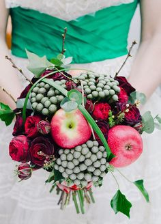 Apples add a fruity punch to this bouquet of red roses and green berries that seamlessly salutes the season. Fall wedding flowers