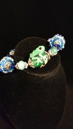 Check out this item in my Etsy shop https://www.etsy.com/listing/386527664/green-frog-lampwork-bracelet-size-65