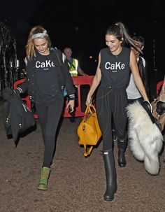 Cara Delevingne and Kendall Jenner showed off their matching CaKe graphic tees and selected bright accessories like Cara's green work boots and Kendall's mustard duffle bag at Glastonbury.