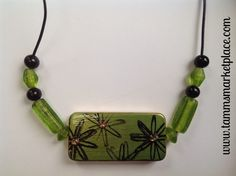 This necklace's beautiful pendant was once a domino! But has now been painted, stamped, jeweled and sealed to transform it into an original piece of art. Back side is photographed to show domino tiles