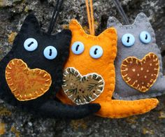 Handmade felt cat ornaments for Autumn, Fall or Halloween decor. A set of three little cats made of grey, orange and black felt with appliqued hearts and button