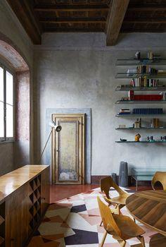 La maison de Roberto Baciocchi en Toscane Dans La salle à manger, des étagères en verre rétroéclairées, une table et un buffet en cerisier dessinés par Roberto Baciocchi en 197 des chaises Jason de Carl Jacobs (circa 1950) et un tapis français des années 1980 apportent un esprit chaleureux à la pièce.