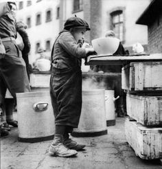 William Vandivert: A young Russian child getting something to eat in a Displaced Persons Camp during World War II, Germany, April 1945.