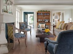 Love the chairs! Add an element of surprise. At first glance, this living room minds its manners, from the classic palette to the blue and white china in the hutch. Then your eye zooms to the pair of chairs by the fireplace. Casual fabrics in indigo and olive cloak the seats and the backs, providing a wonderful contrast to the ladylike frames and turning the classic composition on its ear.