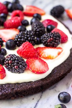 Side angle shot of Fruit Brownie Pizza. A circular brownie, frosted with cream cheese topping and decorated with strawberries, blackberries, raspberries & blueberries.