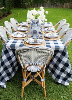 Gingham/buffalo check outdoor dinner party with blue and white chinoiserie ginger jar floral arrangements and French bistro chairs.