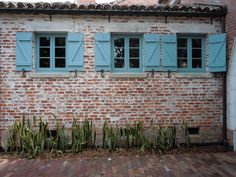 The three windows of the kitchen, adjacent to the driveway, the porte cochere, framed with the gorgeous muted red bricks, the distinctive blue shutters . . . . Casa Feliz, the wonderful home designed and built by James Gamble Rogers, now on Park Avenue, Winter Park, Florida.
