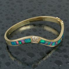 Flowing curved 14 karat gold and diamond bracelet inlaid with Australian opal.