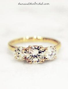 Round diamond 3 stone engagement ring in yellow gold.