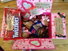 """Long distance valentine care package: """"I have lots of Reisens to love you"""" REISENs, """"Lots of kisses from me to you"""" chocolate kisses, """"Love you to pieces"""" Reese's pieces, """"I love you berry much"""" strawberry licorice, """"message in a bottle"""" flash drive video messages to open when, """"You're my cup of tea"""" custom sharpie mug, """"Hooked on you"""" sour worms, """"You make my heart beat faster"""" coffee, """"I'm a sucker for you"""" heart shaped suckers."""
