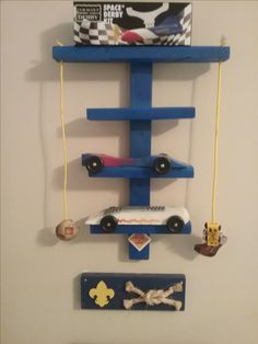 Use inexpensive firring straps to create a display for pinewood derby cars.  Leave the top one long and thread with paracord to create a woggle hanger.