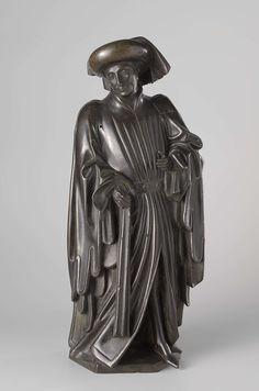 anoniem | Ten weepers from the tomb of Isabella of Bourbon, attributed to Renier van Thienen, c. 1475 - c. 1476 | Hij staat met het linkerbeen naar voren en heeft het hoofd naar links gewend. Hij draagt een bourrelet met afhangende lap en afhangende lamfer, waarvan hij het onderste deel met de rechterhand vasthoudt. De linker armhoudt hij gebogen naast het lichaam, de hand iets daarvan af. De lange met bont gevoerde houppelande hangt tot op de grond en heeft aan de voorkant een split…