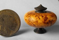 Jeff Spera - Hollow turned from Exhibition Grade Black Ash Burl, this pedestal vessel features a base and removable lid of African Wonderstone; sold on ebay for $25