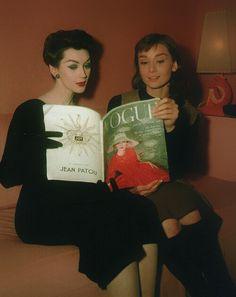 Dovima & Audrey Hepburn reading a copy of Vogue magazine, 1957