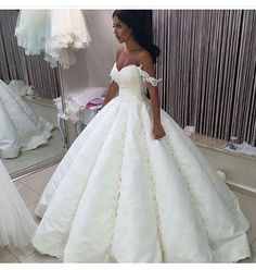 This slightly off the shoulder wedding gown has incredible lace detail that create a fashion masterpiece. The pleating of the ball gown skirt and the princess style of the bridal dress are amazing. We can recreate haute couture wedding dresses like this in a less expensive version for brides on a budget. We can work from any picture you have for inspiration for your custom dress or replica. Get pricing on custom wedding dresses & replicas. Go to www.dariuscordell.com