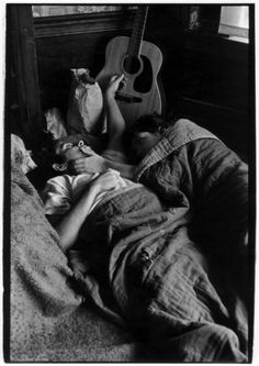 Hippie couple in bed with guitar in background. © William Gedney