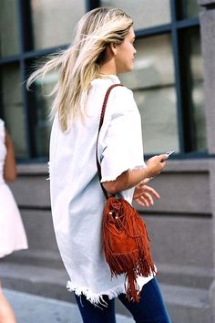 White top with raw hem, fringed suede tote bag and jeans