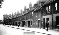 Prince Street, Deptford, 1931.These early eighteenth century houses were known as New Row for a century, before more sensibly taking their place as part of Prince Street.They must have been built with shipbuilders in mind, as the main gate of the Deptford Royal Dockyard was just around the corner.The old houses originally extended to opposite the dockyard gate, but the ones in the distance, including the Tiger Cat pub, were rebuilt in the 1880s.The new houses and the pub were destroyed…