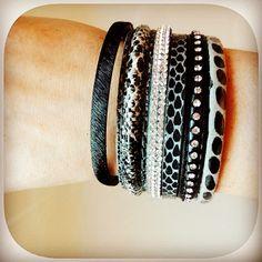 Pulsera en color negro y gris, compuesta de varias pulseras unidas, con detalle de strass. Cierre de imán
